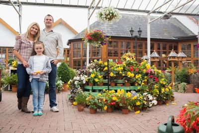 Image of parents standing in a flower-filled garden center, with their daughter standing in front of