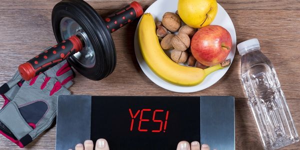 scale says yes! healthy foods, apples, banana, walnuts on a plate, exercise wheel, gloves and water