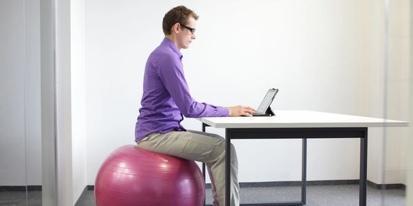 Man sat on a fitness ball at a desk on his computer