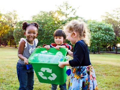 Three young children, girls and a boy, are smiling and holding a recycling bin of plastic bottles.