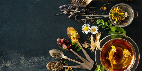 golden spoon, tea, strainer, lavender, chamomile, calendula, arnica, rose, peppermint, verbena, linden, hot infusion, dry flowers, fresh flowers, black table, glass cup