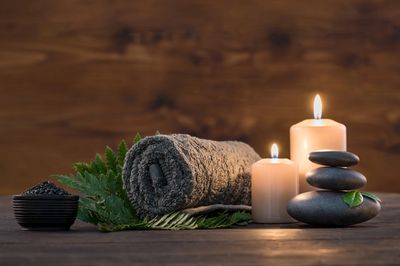 Rolled towels, lit candles and stacked hot stones.