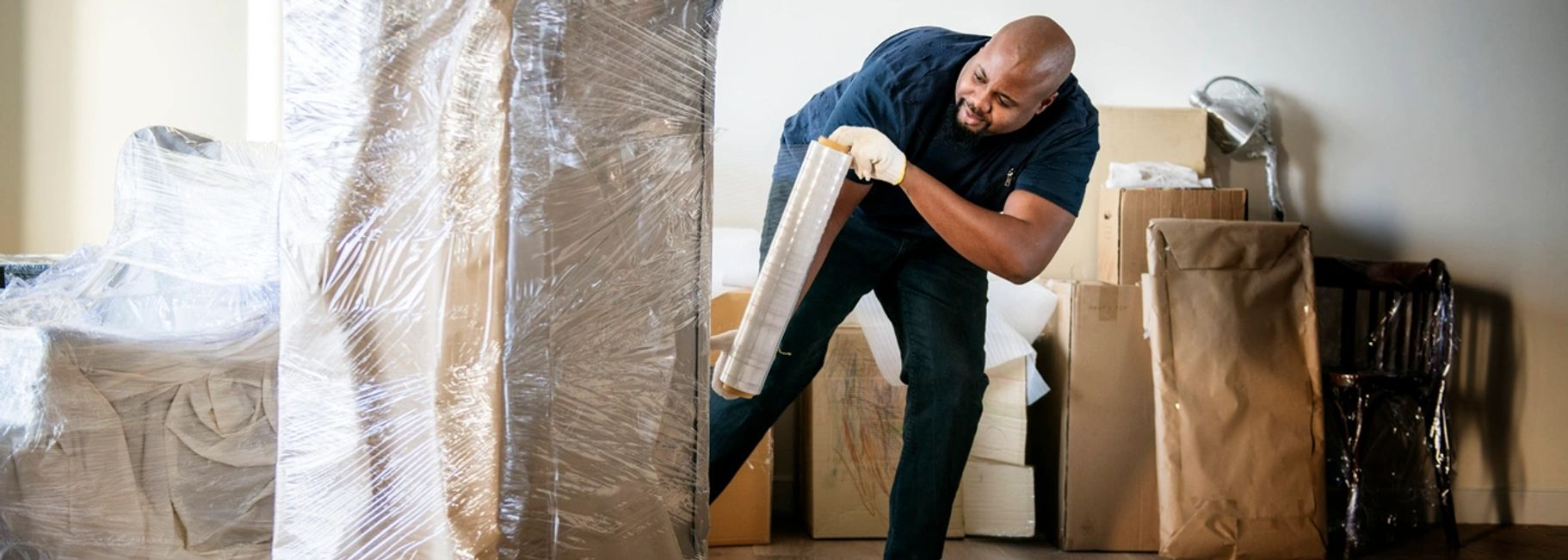 A mover protecting a sofa with thick paper then stretch wrapping it in the living room