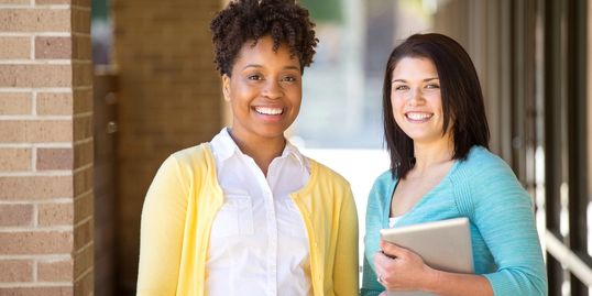 Two femme presenting people stand outside of a building, one has a notebook. They're smiling.