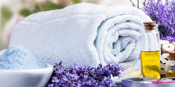Spa towel with body scrub essential oil aromatherapy lavender and tealight candles