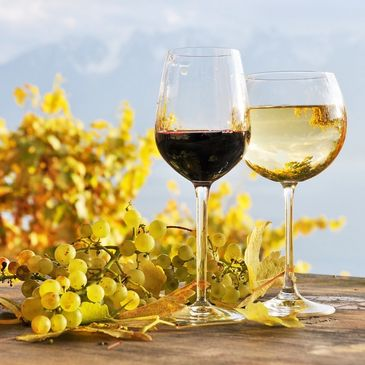 2 wine glasses, 1 red, one white wine. Green grapes and leaves on wooden table