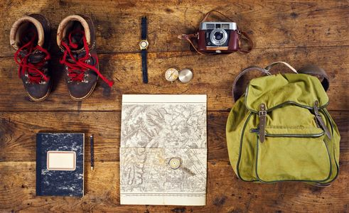 This photo contains images of a Map, Travel items, backpack, camera, journal, compass, hiking boots.