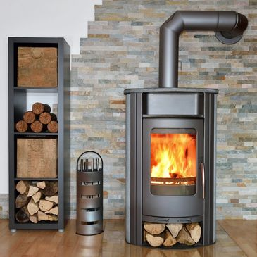 A Epa certified Wood stove burning and heating the home with wood logs close by