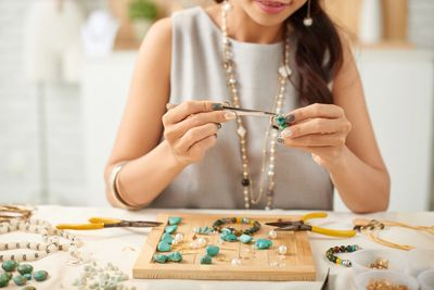 Woman in studio workshop hand-making jewelry. Learn about our limited and one-of-a-kind jewelry.
