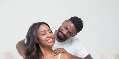 a black man with short hair and beard wearing a white t-shirt giving a black woman with long, wavy hair wearing a white tank top who is looking back at the man. Both are smiling.