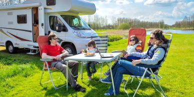 family relaxing next to a caravan