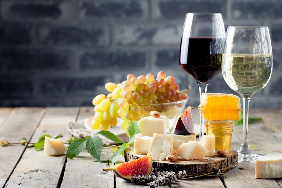 Margaret River Wine Tasting Tours. 2 glasses of wine on wooden table next to cheese board.