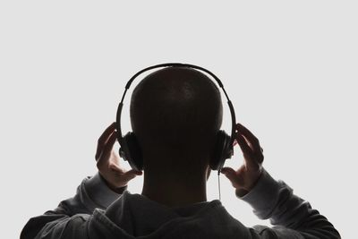 Top part of bald student wearing a hoodie holding headphones with his hands