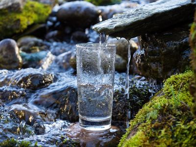 Glass filling with pure natural water from river