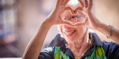 Older white haired woman with fingers in a heart shape.