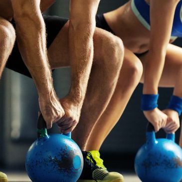 Fortnight pass a man and a woman bend, each holding a heavy blue kettlebell in their hands