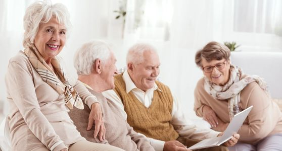 Senior citizens smiling and looking at a laptop together.