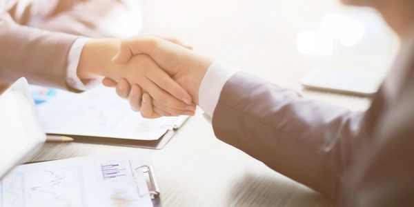 Man and woman shaking hands at a business meeting.