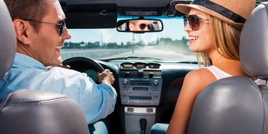 man and woman driving in a car with polarized sunglasses on