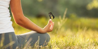 A lady sits meditating, a butterfly rests as she quietly listens.Meditations accompany our range