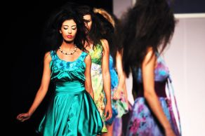 Women models in dresses walking the runway at a fashion show.