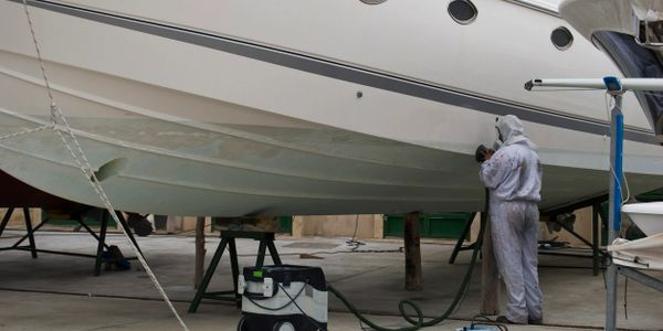 Hull preparation (sanding and scraping) for paint application on saltwater boats.
