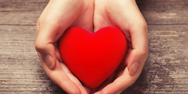photo of a blastic red heart held in hands with a giving motion.