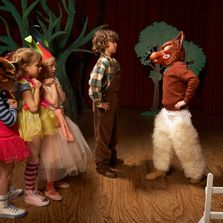 Children are dressed in costumes bravely confronting one child dressed as a wolf.