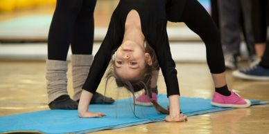 Child practicing backbend on yoga mat.
