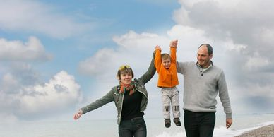 Parents walk along the beach with child and playfully lift him in the air