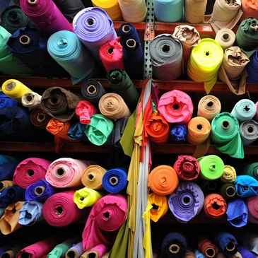 Lots of bright coloured rolls of fabric on shelves