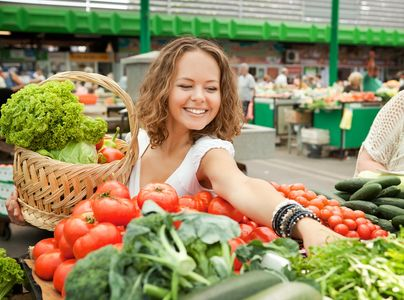 Woman buying produce at open farmers market.