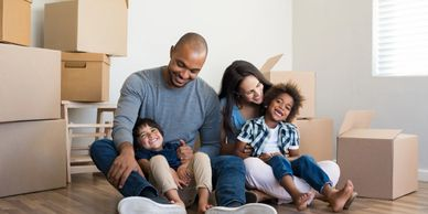 a family sits on the floor while moving with packed boxes