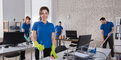 woman smiles and cleans in blue shirt in an office environment