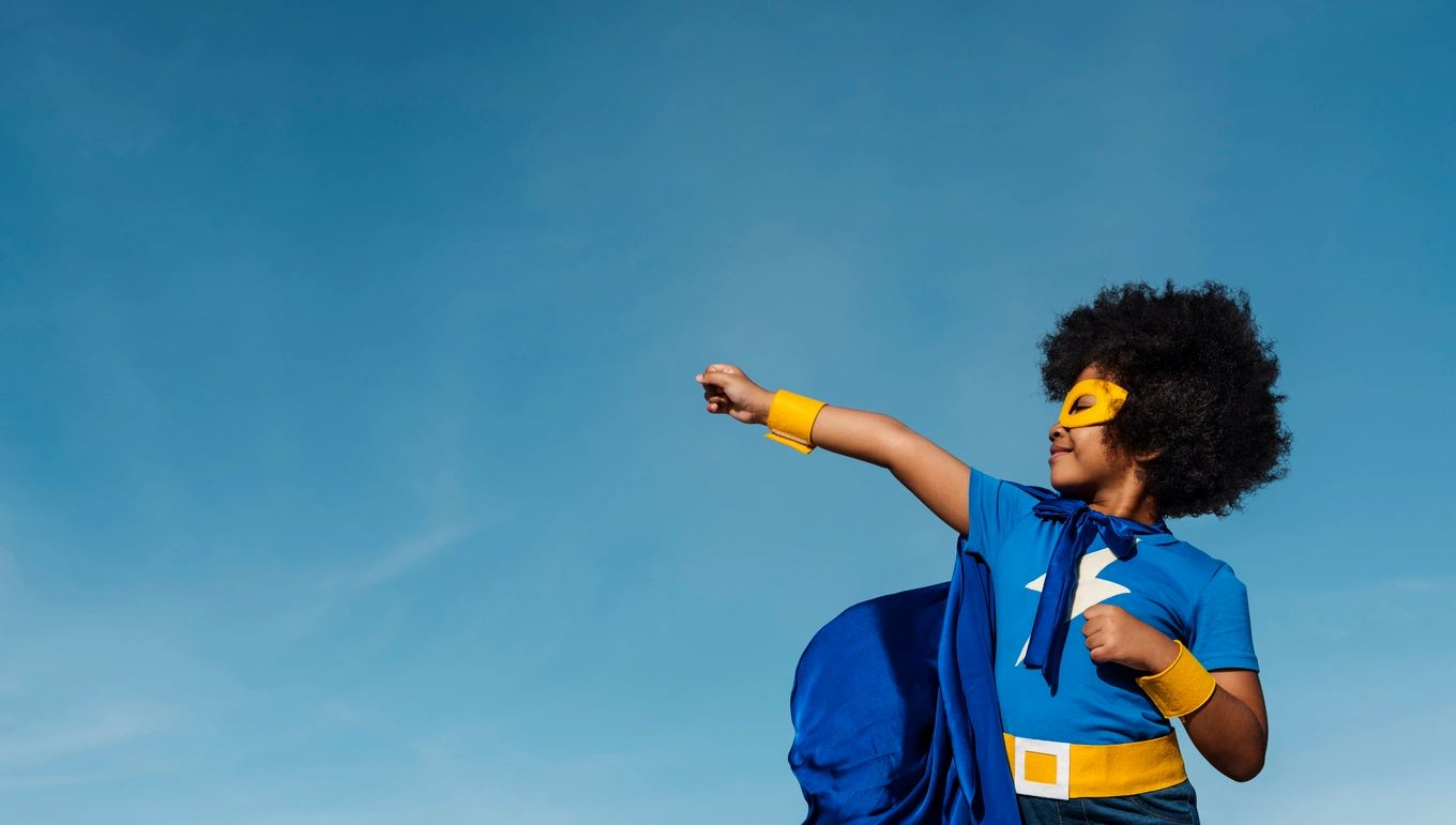 A young girl dressed in a blue and golden superman/superwoman costume with her fist in the air.