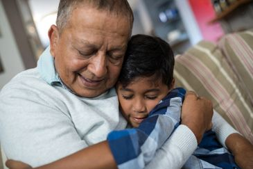 an Indian grandparent and his son hugging on a couch. www.newfamilyfoundation.org