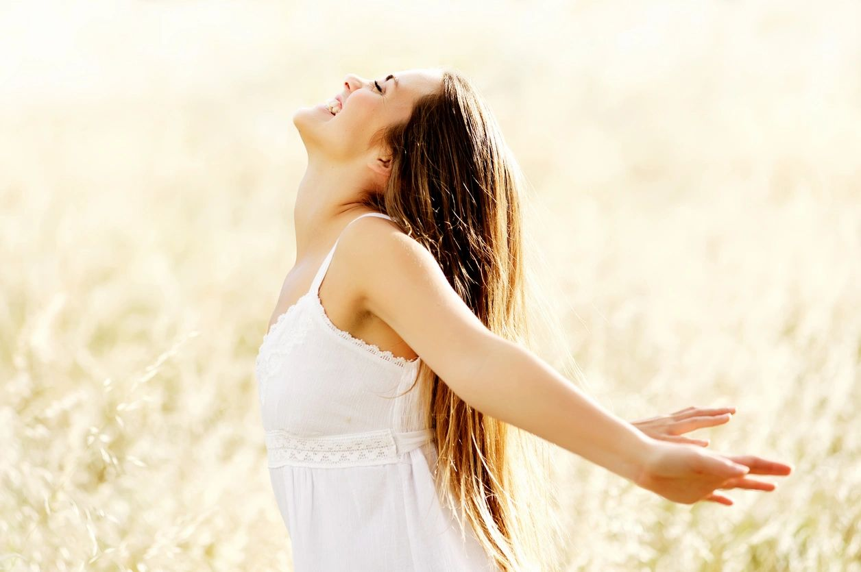 Healthy woman showing her joy and energy by facing the sky and smiling. Clear skin and shiny hair.