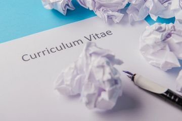 "A white page entitled ""Curriculum Vitae"", with screwed up pieces of paper and a fountain pen."