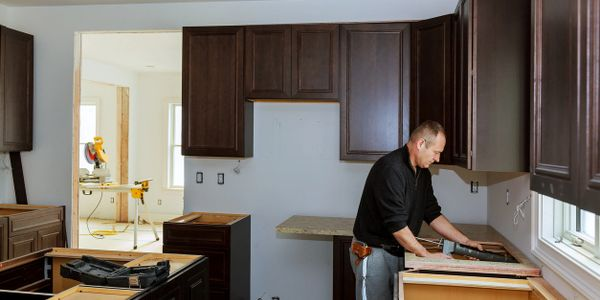 picture of  man installing new countertops in a kitchen remodeling job.