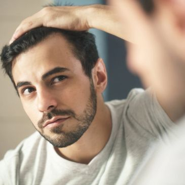 Man looking in the mirror at his growing hair