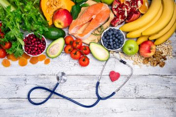 Healthy, colorful vegetables and fruit with a piece of salmon and a stethoscope laying on a table.