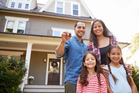 family standing in front of home holding keys