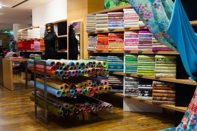 Fabric store with many colored fabrics for sale on display