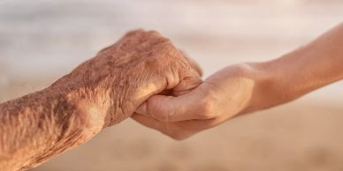 elderly person clasping a younger adults hand relating to power of attorney at protect and prosper.
