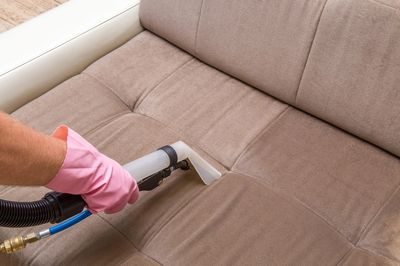 Person Steam Cleaning Upholstery