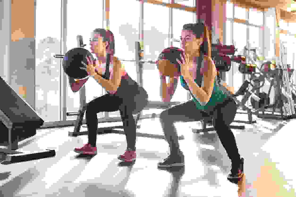2 women exercising by bending at the knees and holding