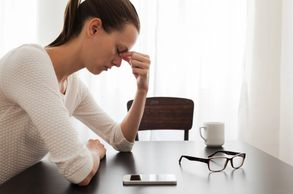 Woman looking stressed at her desk with her head down, glasses off, massaging forehead