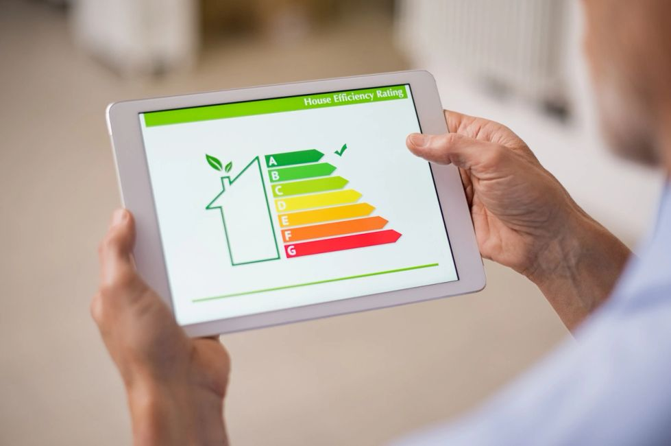 picture of a man holding a tablet with home energy ratings displayed.