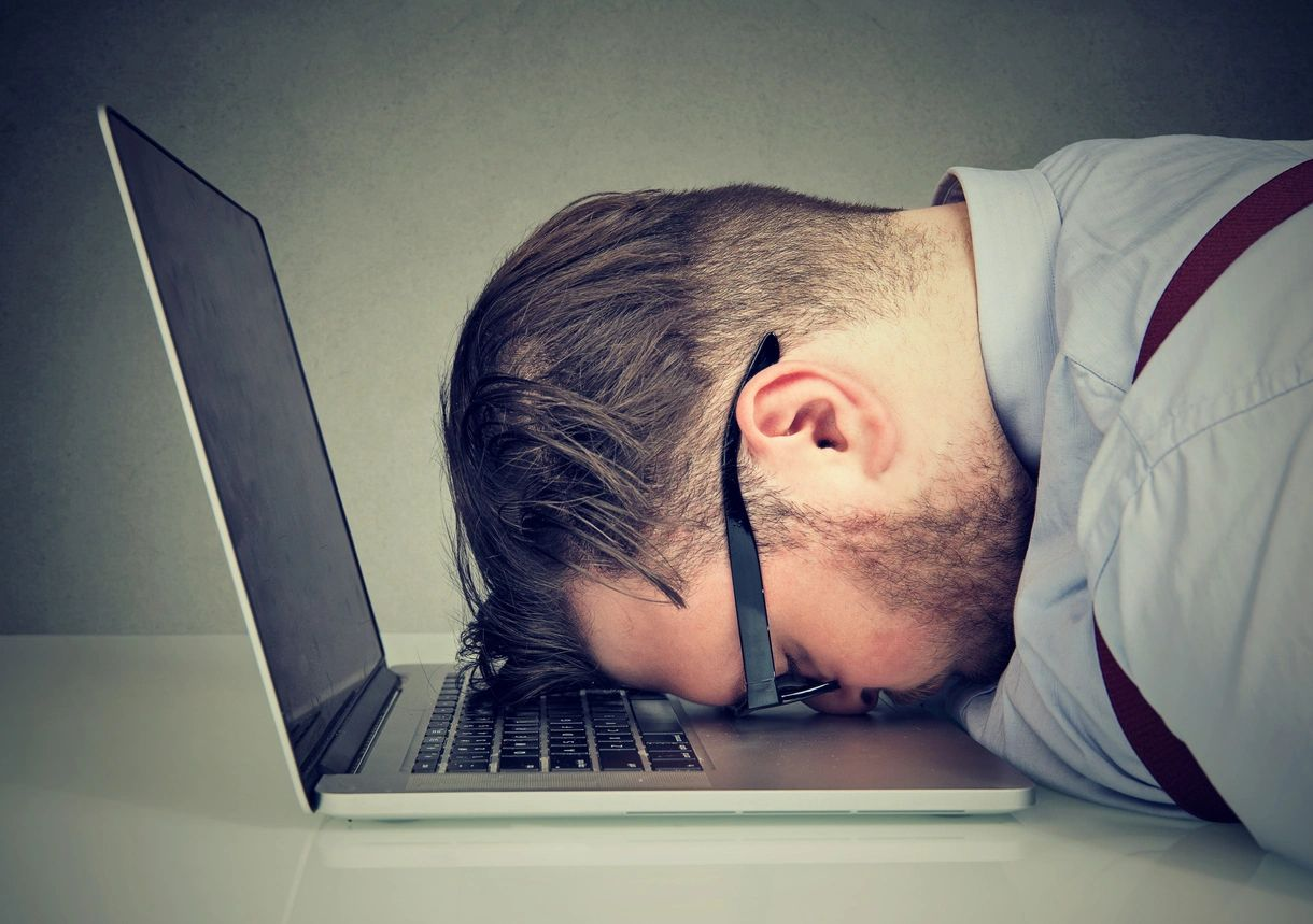 Man banging his head against his laptop.