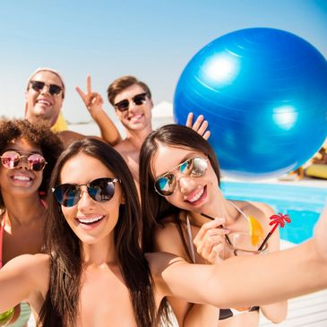 Small group of friends at the beach in swimwear holding a big blue ball and looking at camera